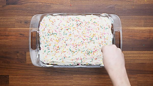 frosted cake being topped with sprinkles