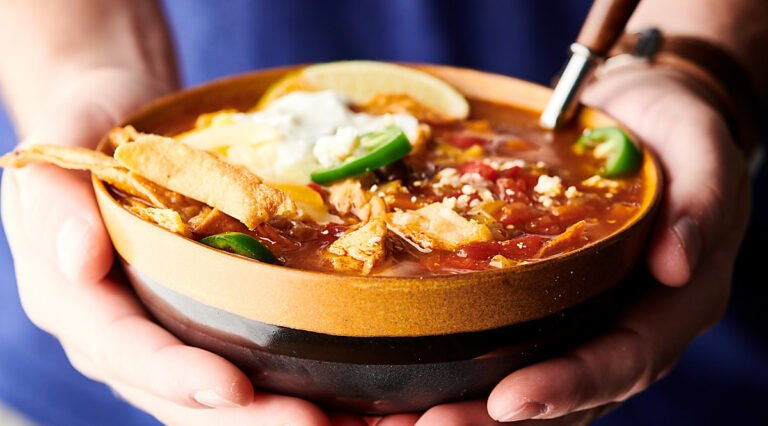 bowl of instant pot chicken tortilla soup held two hands