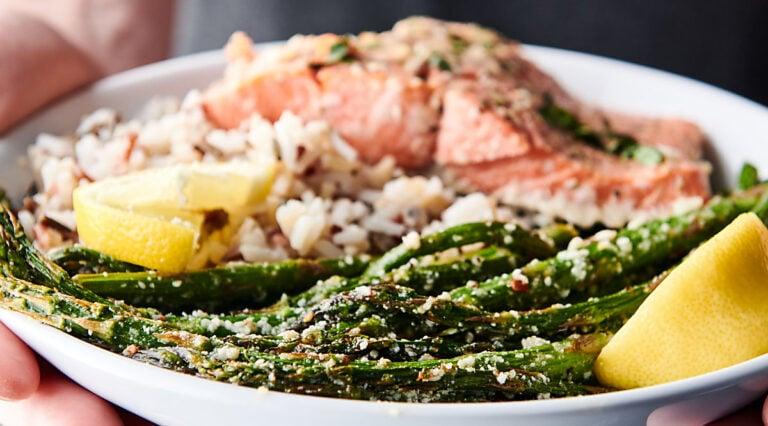 lemon parmesan roasted asparagus on plate with salmon held