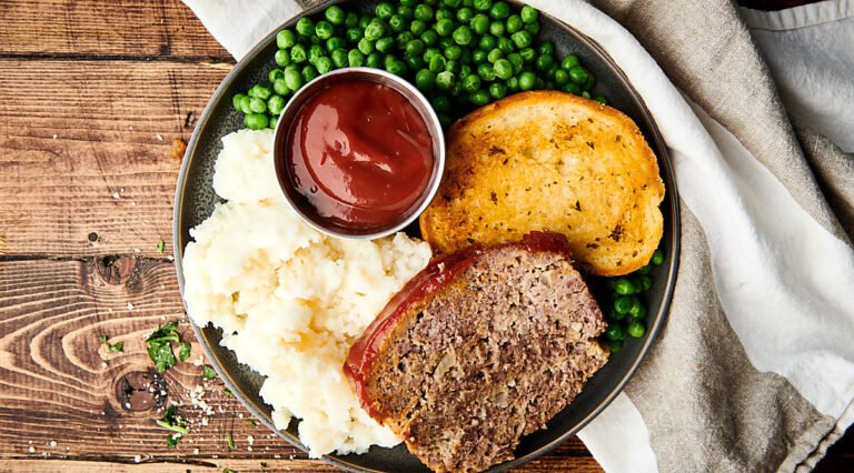 meatloaf on plate with bread, potatoes, and peas above
