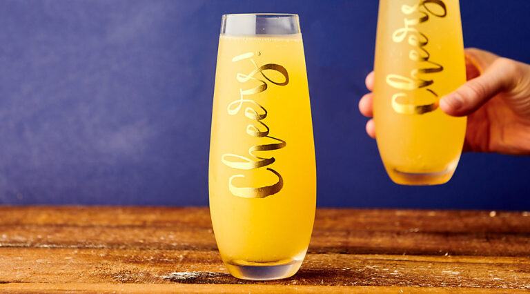 two glasses of mimosas, one held