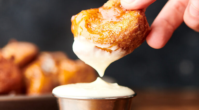 monkey bread being dipped into frosting