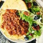 spaghetti bolognese on plate with salad and garlic bread above