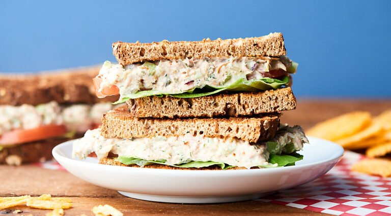 two halves tuna salad sandwich stacked on plate