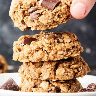 vegan oatmeal cookies stacked on plate, one being lifted off