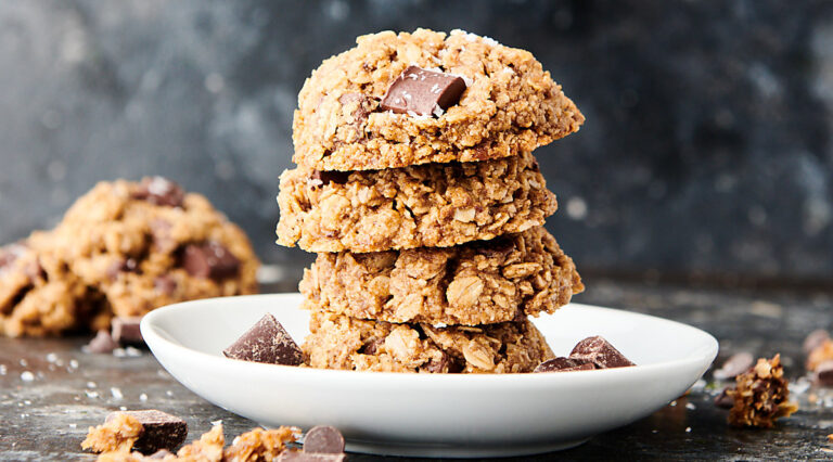 four vegan oatmeal cookies stacked on plate