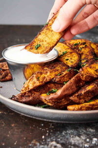 air fryer potato wedges on plate, one being dipped in sauce