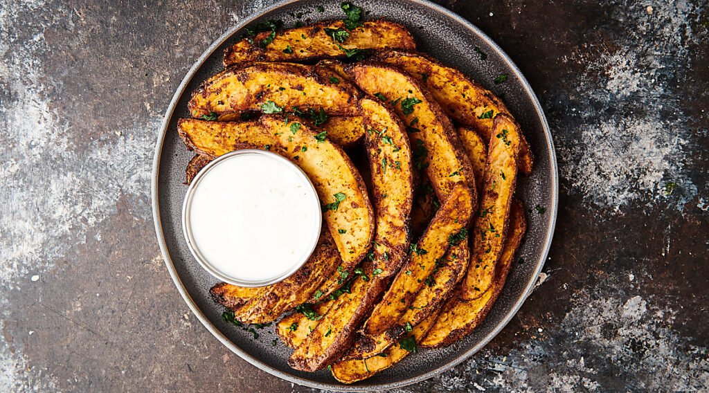 air fryer potato wedges on plate above