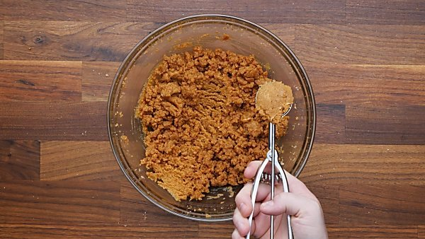 cookie dough being scooped with small cookie scoop