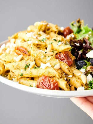 plate of sun dried tomato pesto on pasta with side salad held