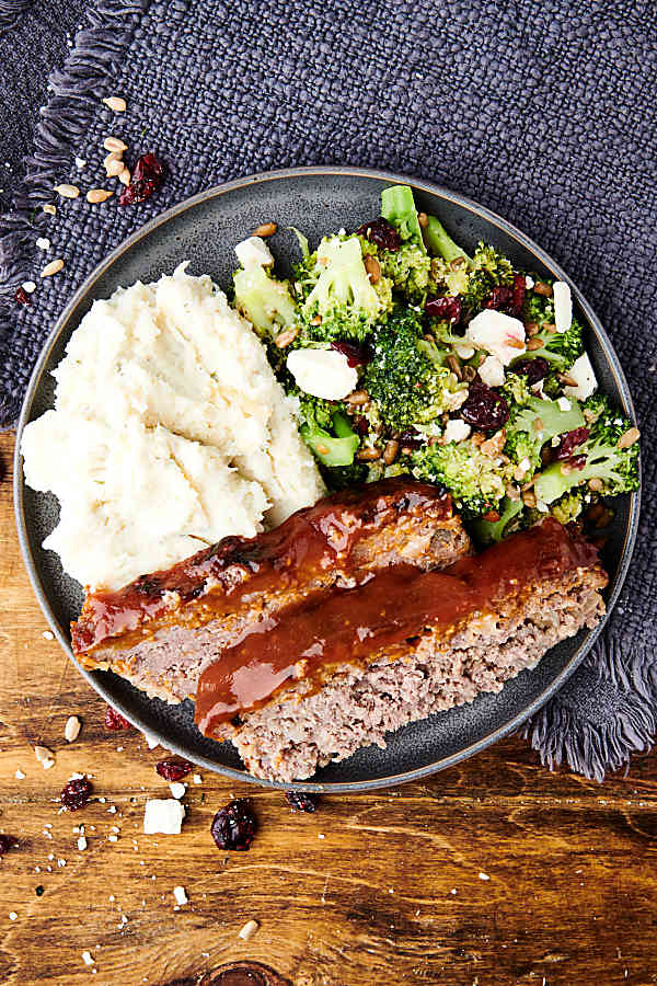meatloaf on plate with mashed potatoes and broccoli above