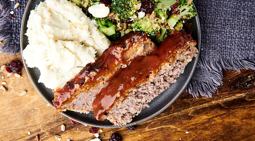 air fryer meatloaf on plate with mashed potatoes and broccoli above