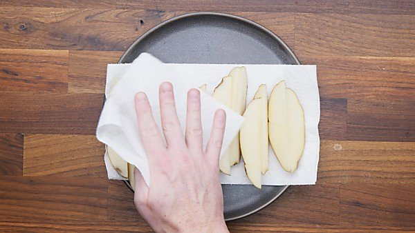 potato wedges being dried on paper towels