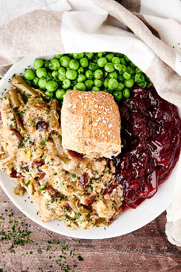 crockpot chicken and stuffing on plate with cranberry sauce, peas, and dinner roll above