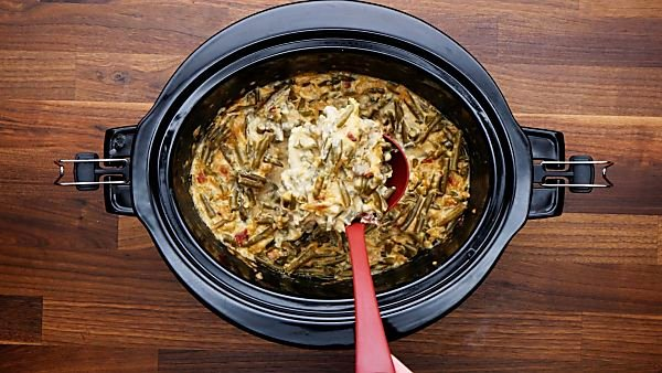 green bean casserole topped with fried onions being served with ladle