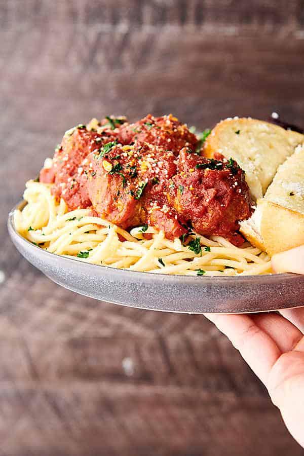 plate of crockpot turkey meatballs over pasta held