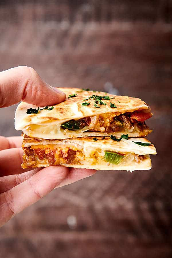 two slices of pizza quesadilla held