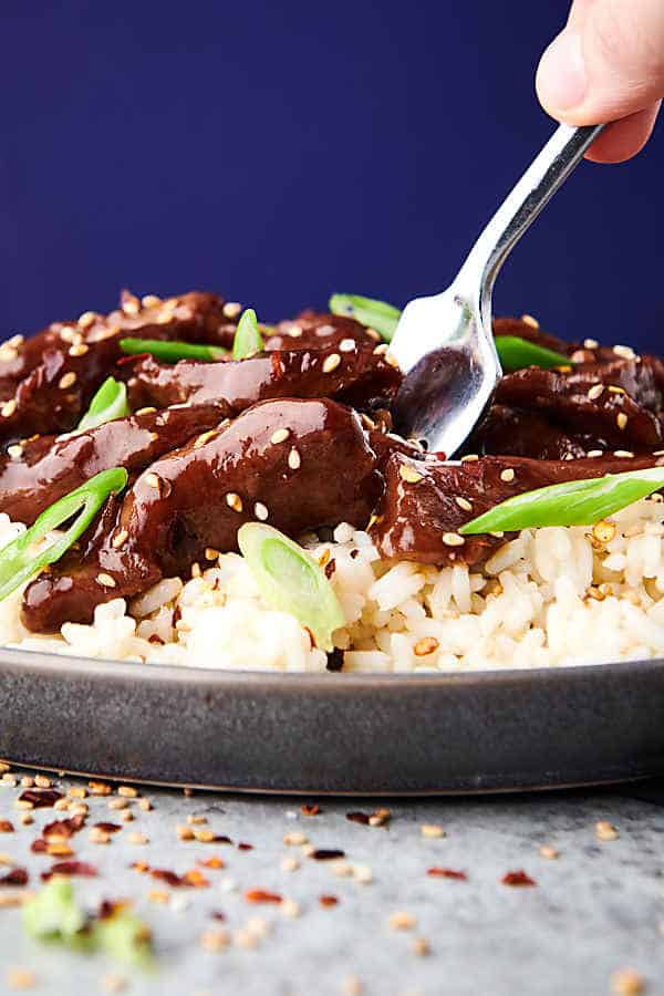 closeup of slow cooker mongolian beef on plate over rice