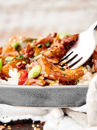 fork in plate of sweet hawaiian crockpot chicken side view