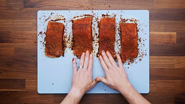 spices being rubbed on salmon