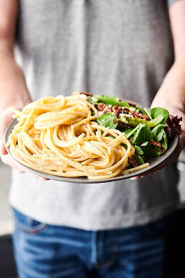 plate of cacio e pepe held two hands