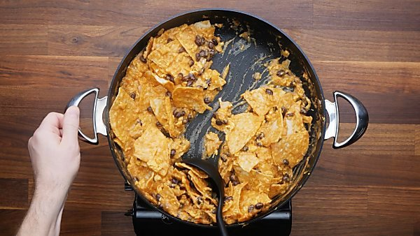 finished chilaquiles in skillet being scooped with ladle