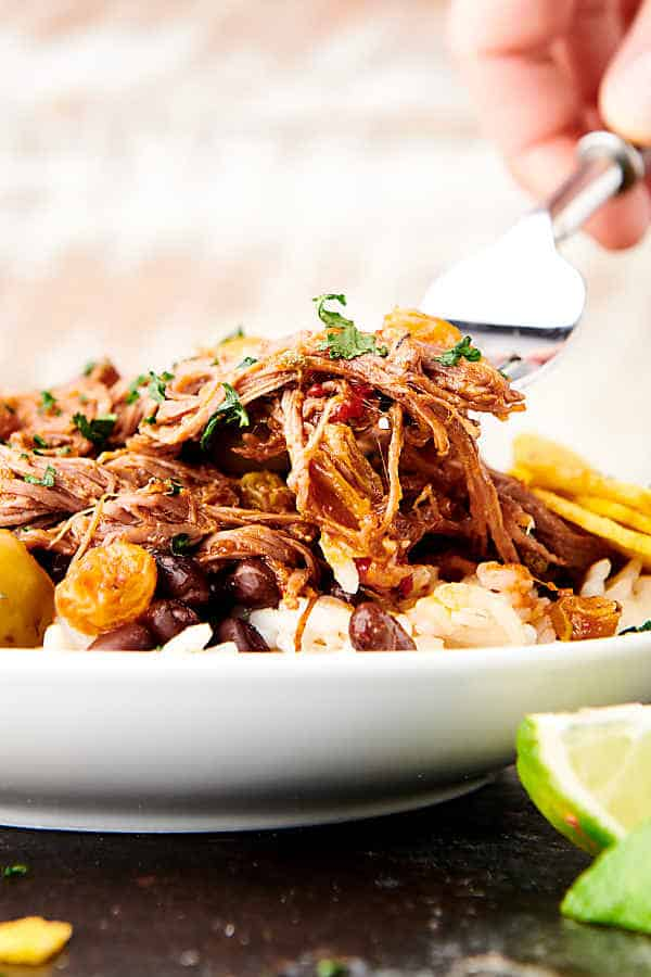 forkful of ropa vieja being lifted off plate