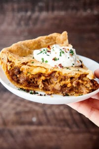 slice of meat pie on plate held