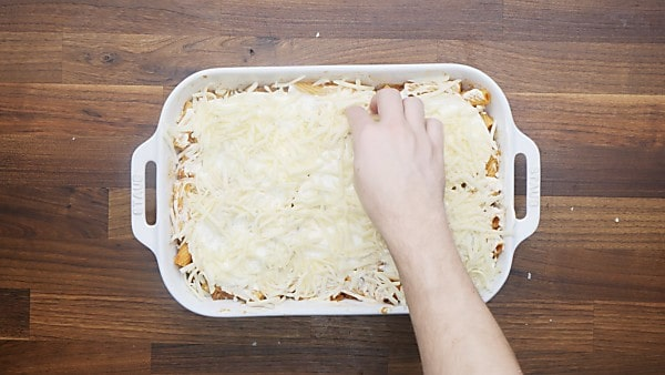 rigatoni pasta being layered with cheese in baking dish