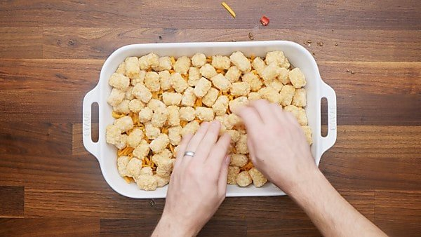 tater tots being layered in casserole dish