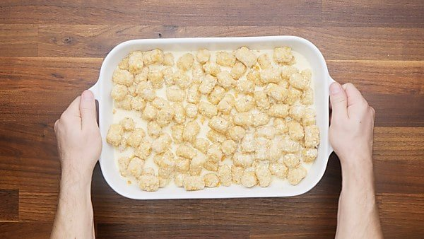uncooked, assembled tater tot casserole in baking dish