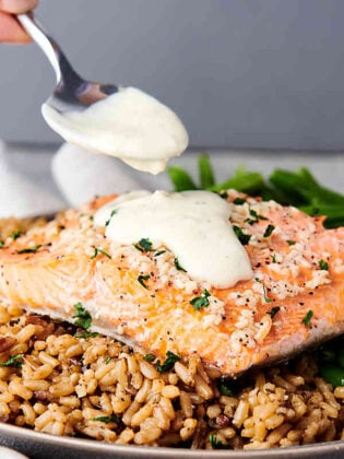 baked salmon over rice being drizzled with honey lemon sauce