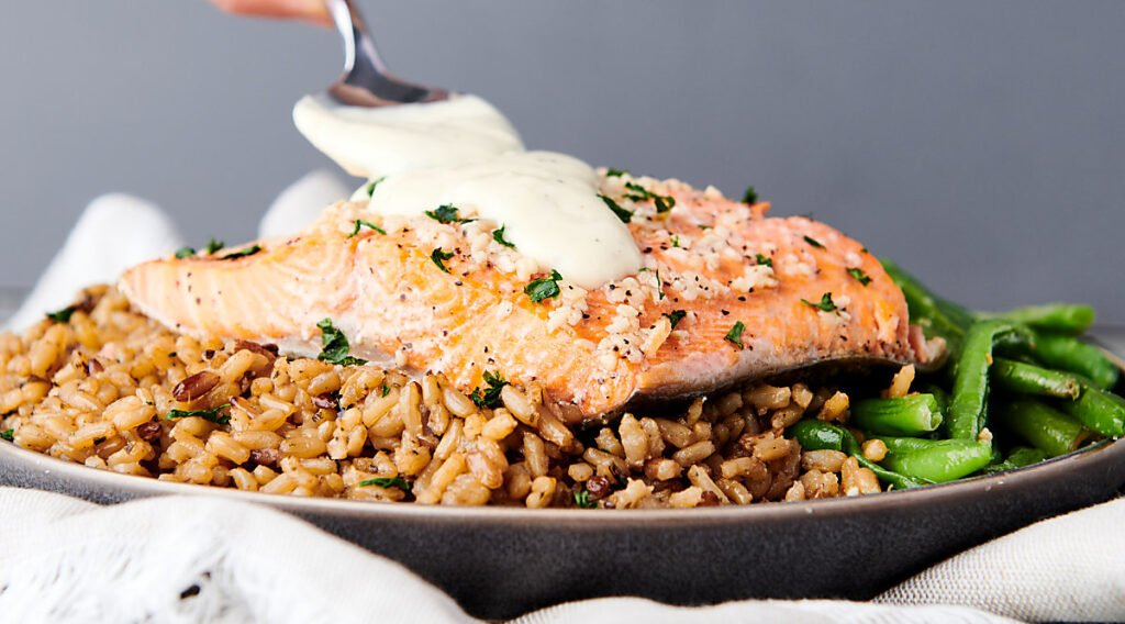 honey lemon sauce being drizzled over baked salmon