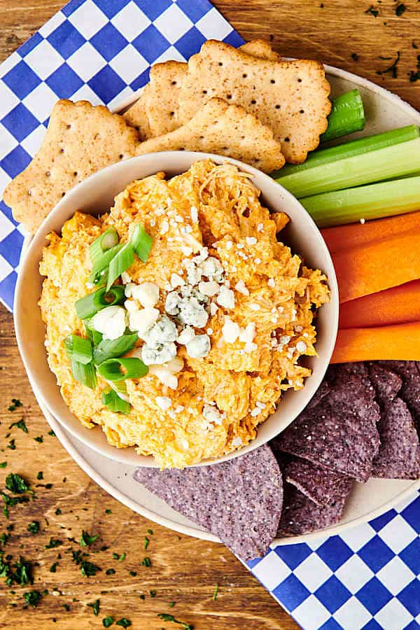 bowl of buffalo chicken dip on plate with crackers, chips, and veggies above
