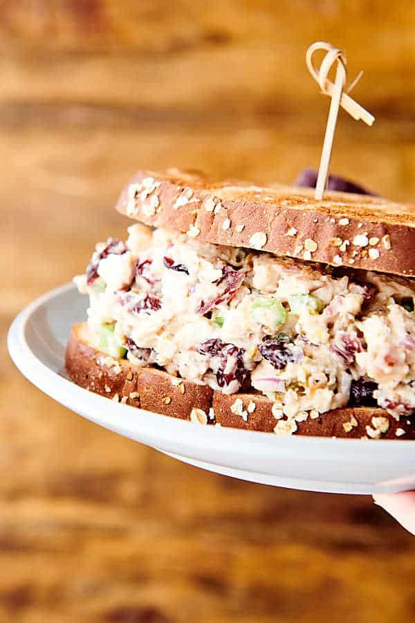 cranberry chicken salad sandwich on plate held
