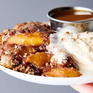 plate of crockpot peach cobbler held