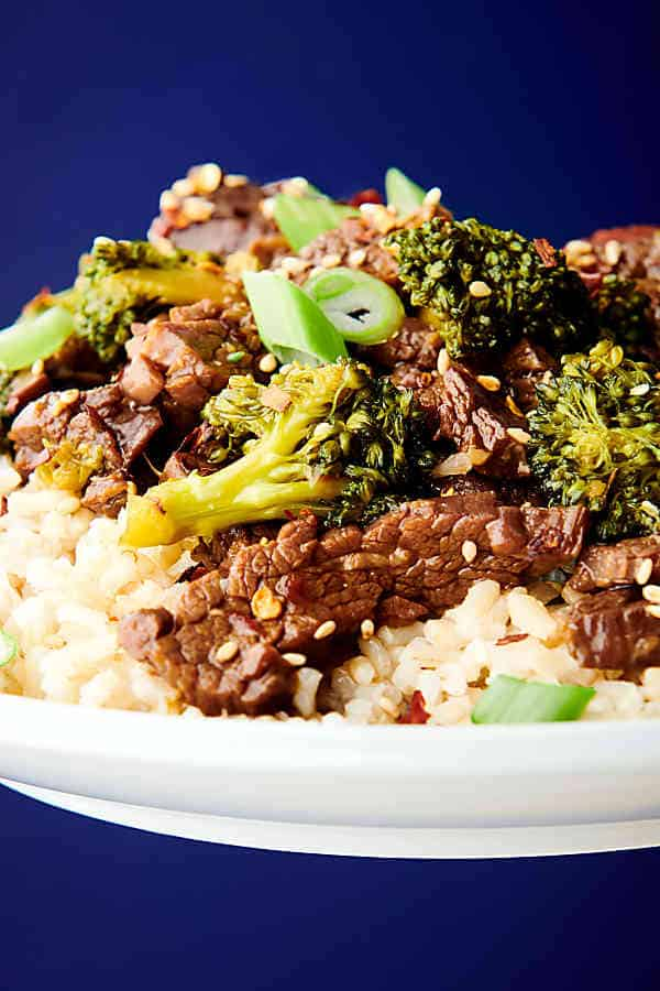 plate of instant pot beef and broccoli over rice held