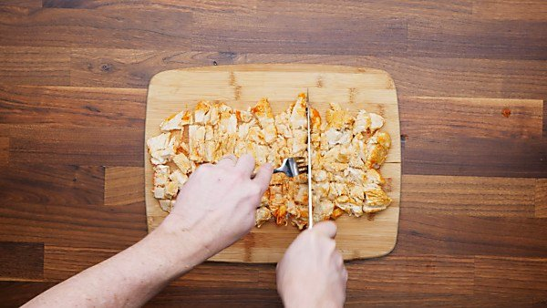 chicken being cubed on cutting board