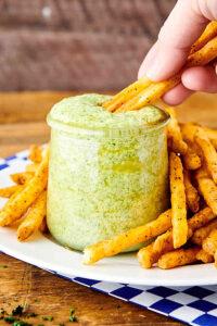 fries being dipped into pesto aioli
