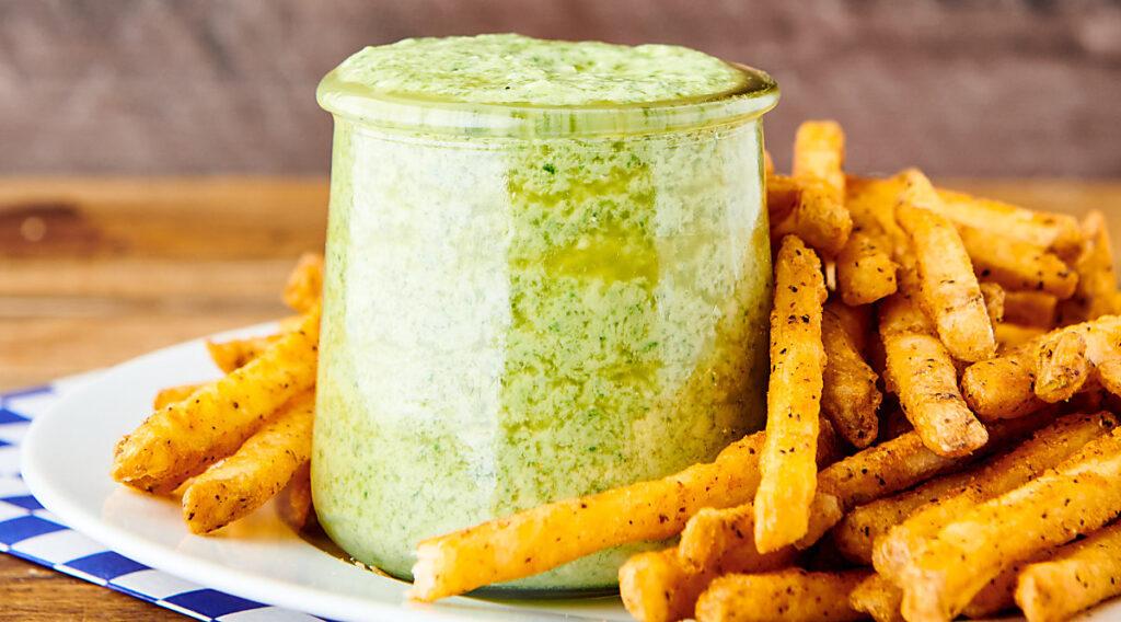 jar of pesto aioli on plate with fries