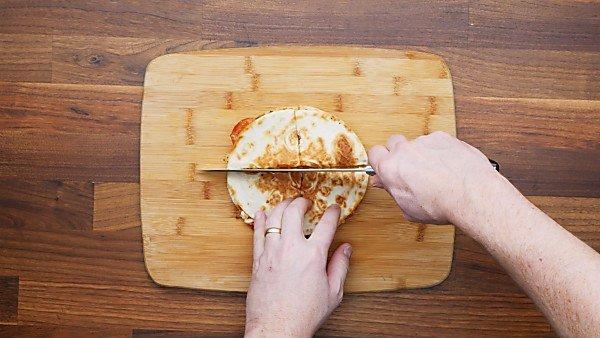 pizza quesadilla being sliced on cutting board
