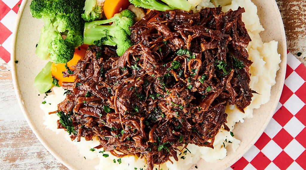 slow cooker flank steak over mashed potatoes with veggies above