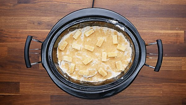 butter and turbinado sugar over peach cobbler ingredients