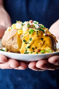plate with instant pot baked potato held two hands