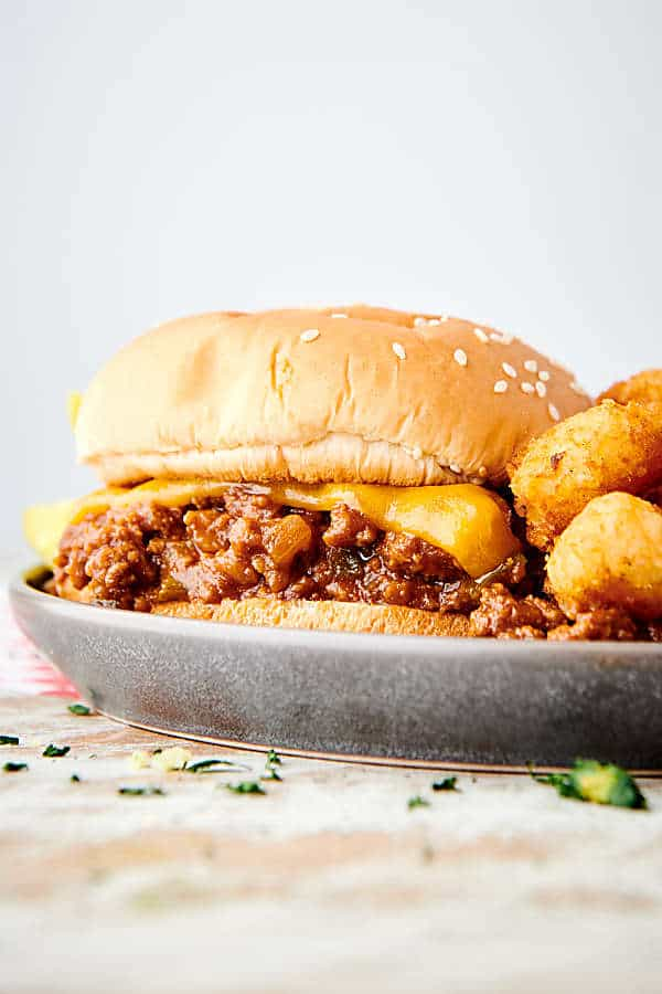 instant pot sloppy joes sandwich on plate with tater tots