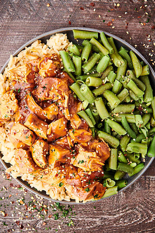 plate of crockpot bourbon chicken with green beans above