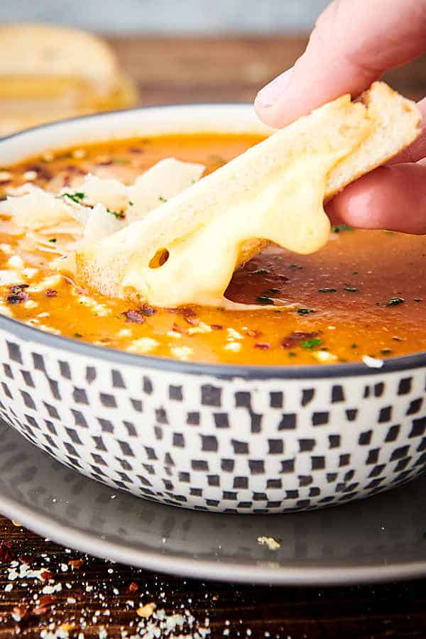 bread being dipped into bowl of tomato soup