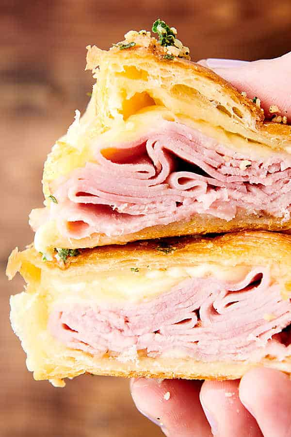 two halves of ham and cheese croissant held