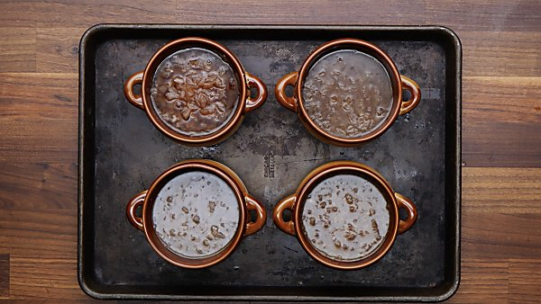 instant pot french onion soup in four bowls on baking sheet