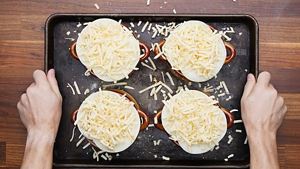 croutons and cheese on bowls of french onion soup